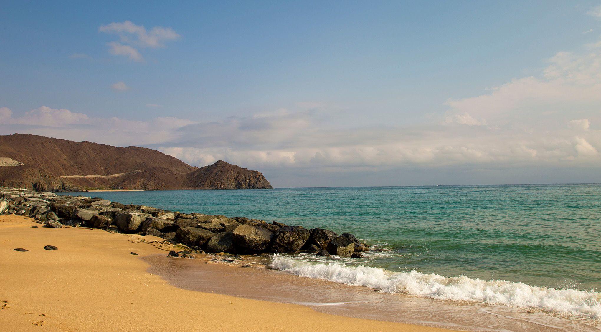 Goldgelber Sand, leuchtend blaues Meerwasser, braunrote Felskuppen –an der Küste von Fujairah